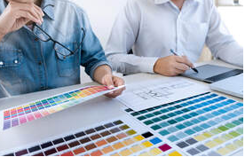 Two men in Granby are looking at color palettes. There's an architect's plan on the table.